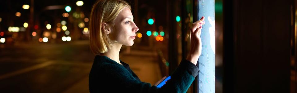 Woman using a digital signage kiosk on city streets in Boise, Idaho
