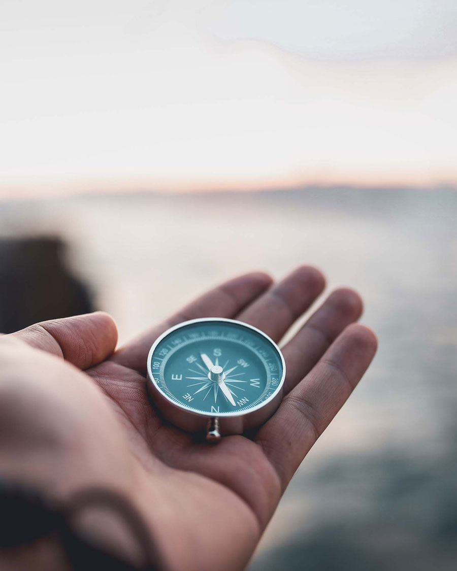 a hand holding a compass with a blurry background